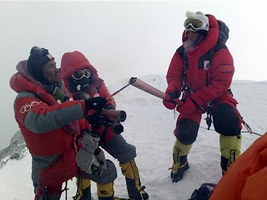 Norbu Zhamdu lights the Olympic torch of Everest torchbearer Gegyi.